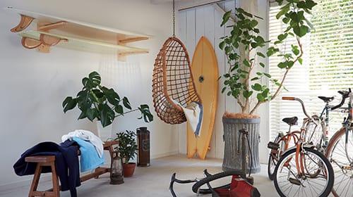 写真:部屋のインテリア。ハンモックタイプの椅子や自転車、壁にかけたサーフボード